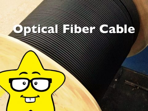 Black sheathed optical fiber cable on a wooden drum